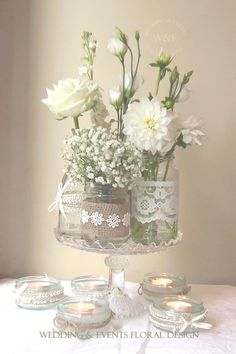 An all White display of flowers in Lace & Hessian wrapped Jars & Bottles by Wedding & Events Floral Design www.weddingandevents.co.uk
