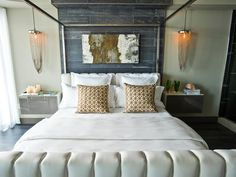 French hotel-style linens dress the bed, topped with lattice overlay throw pillows and flanked by two chain-link pendant lights.