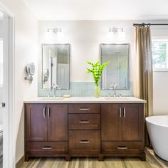 This master bathroom features a large double vanity and his and hers mirrors and lighting for a custom feel. A drawer at the bottom of the sink compartment provides additional storage that is typically unusable due to plumbing. A beautiful glass tile backsplash completes the space.