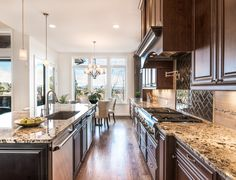 Dark stained kitchen cabinets paired with gorgeous speckled granite in Colorado - love the herringbone accent backsplash behind the stove top! #DRHorton #FindYourHome
