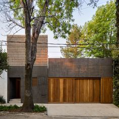 A patchwork of pale mud brick, teak wood and texture black walls fronts this house in Mexico City, which architecture studio DCPP has designed around a pair of patios.