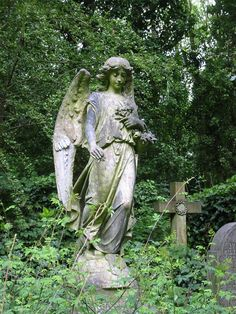 A statue of an angel stands atop a grave in Highgate Cemetery, London.