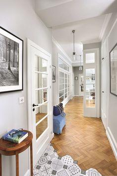 Przeszklone drzwi do salonu były wzorem dla stolarza, który dorobił pozostałe skrzydła, zachowując ten sam podział szyb. Ozdobne klamki są z firmy Barcz. Płytki na podłodze to hiszpańska mozaika.