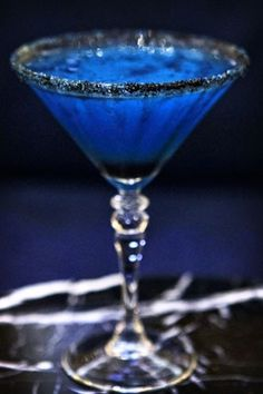 Blue cocktail - Witches brew: Bacardi Dragon berry rum, Blue Curacao, Creme de banana, fresh squeezed lime juice, served up in a martini glass rimmed with black sugar.