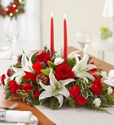 Traditional Christmas Centerpiece - Large. Put holiday magic on the table with our truly original, traditional centerpiece arrangement. Decked to delight with white lilies, red roses, and red and white carnations, it features enchanting accents of pinecones and fragrant evergreens like holly, pine and cedar. To complete the picture postcard beauty of this seasonal surprise, our florists add red velvet ribbon and a tall, red taper candle. Hand-crafted arrangement of roses, lilies, carnations…