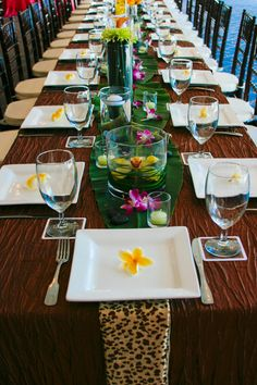 tropical table- leaves in the center (but more artistic in layout) w turquoise color rocks and loose orchids .