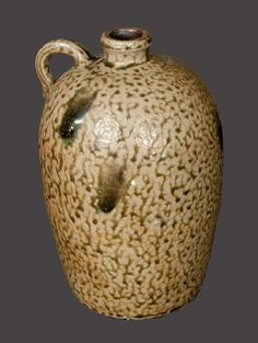 """Alkaline-Glazed Stoneware Jug, North Carolina origin, late 19th century, ovoid jug with short rounded spout and small handle, the surface covered in a mottle greenish alkaline glaze with heavy drips. A few in-the-firing chips to underside. H 9 1/4""""."""