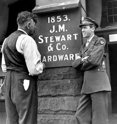 Not published in LIFE. Jimmy Stewart and his dad outside the family hardware store, Indiana, Pa., 1945.
