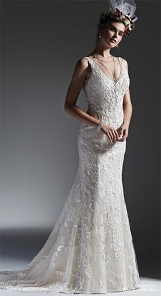 Romantic lace and tulle combine to create this striking sheath wedding dress, accented with glittering Swarovski crystals and shimmering beads. Finished with V-neckline, plunging back and covered buttons over zipper closure.