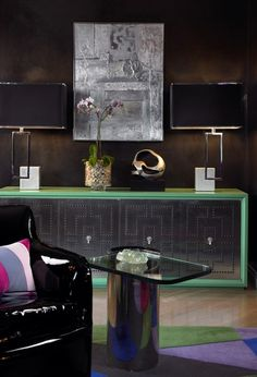 Modern Green Sideboard    A black patent leather chair and reflective side table animate this dark living room.