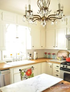 Pretty white kitchen with vintage chandelier and wood countertops