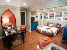 A padded bed frame, wall niche and cobalt blue furniture adds vibrant color and pattern to the space. A corner of this master bedroom is turned into a home office with a traditional table and simple chair. Shelving over the bed provides extra storage and display space.