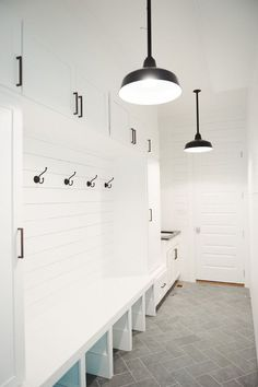 The all white paint with black hooks and knobs provides a traditionally elegant - yet minimalist look- to this entryway.