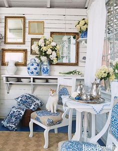 A kitty sitting atop Manuel Canovas fabric in a blue and white chinoiserie dining room. Design: Sally Swing
