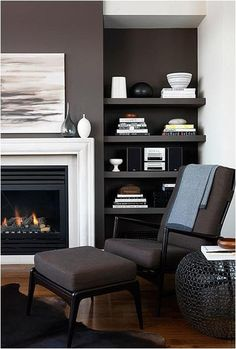 contemporary fireplace....dark walls/shelves on whole wall with white trim around firebox