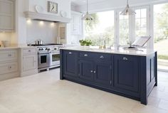 Luxury blue painted kitchen with feature island with full length pantry with personalised engraving and concealed storage.