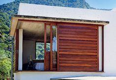 No quarto do casal, a área junto à janela de canto vira uma varanda quando são recolhidos nas laterais os três caixilhos de madeira cumarú e freijó. O de dentro é fechado até a metade, como um guarda-corpo, o do meio tem painel de vidro e o de fora, veneziana