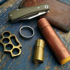 Pocket dump picture with small EDC items, small Lanny's Clip slipjoint from K'roo Knives, copper sleeve for Burt's Bees, brass DQG Fairy flashlight...