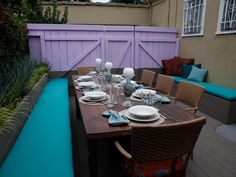 A lavender privacy fence is a pretty backdrop against this outdoor dining area designed by Jaime Durie. Built-in benches with aqua-colored cushions are paired with woven arm chairs to provide plenty of seating while entertaining.