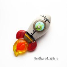 Blasting off!  A lampwork glass bead rocket with alien by Heather Sellers.  #lampwork #alien #rocket #ufo #space #bead