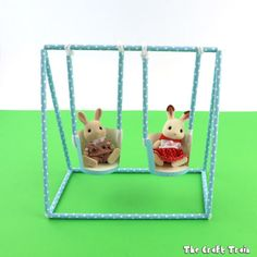Make a simple toy swing set from straws and pipe cleaners with cupcake liner bucket seats. This is a fun STEM or STEAM activity for kids!