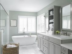 The master bathroom is cool and relaxing, with dove-gray cabinets, his-and-hers sinks separated by a towel shelf, and a deep soaking tub near the windows. A large glass-enclosed shower is on the left. Small floral accents brighten the space.