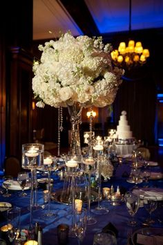 Again I love the lushness. Just substitute some or all of the white flowers with some purple flowers and add feathers to pull together the theme. I also love the hanging crystals and trumpet vase. What do you think?