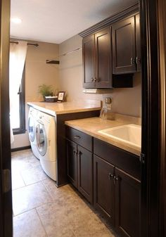Laundry Room. Built-in Folding Counter. Front Load Washer and Dryer. Mudroom Sink. Dark Cabinets.