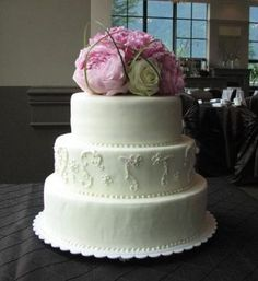 ivory fondant, the dress detail piped in the center, fresh flower topper