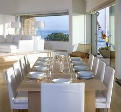 clean white dining area with white upholstered chairs and contemporary pale blonde wood table - open plan to contemporary white living area
