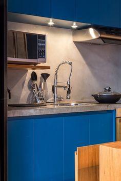 O jeito contemporâneo de viver se reflete na praticidade da cozinha do Apê Cobre Blue, reformada pelo escritório Casa 100 Arquitetura. A bancada em concreto contrasta com o azul da laca nos armários e o cinza do tecnocimento, todos elementos modernos e fáceis de manter