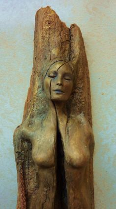 This sculpture of a woman is carved into wood, and appears to be split down the middle. She is naked and her eyes are closed, and it almost seems as though she's tied to the log. This image is visceral and sexualized in a way. It is an interesting choice in portraying the human form.