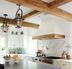 White kitchen, wood beams, wood trim on vent hood, and rustic lanterns. Kitchen Hoods, White Kitchen Cabinets, Kitchen White, Kitchen Ranges, Upper Cabinets, White Interior Design, Interior Design Kitchen, Rustic Kitchen, New Kitchen