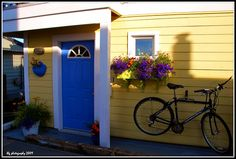 Yellow House with a Blue Door, Flower Box and Bike Yellow House Exterior, House Exterior Color Schemes, Cottage Exterior, Red Houses, Yellow Houses, Tiny Houses, House Front Door, House Doors, Home Door Design