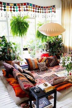 Chic and colorful bohemian living room with lots of plants and natural sunlight