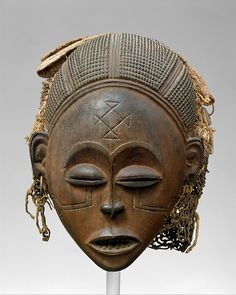 This work is an outstanding example of Pwo, a classic Chokwe mask genre that honors founding female ancestors.  Such representations are especially significant given that the Chokwe trace descent through their mothers' lines. Inscribed motifs on the mask's forehead and cheeks are classic graphic designs that aesthetically enhanced a woman's beauty in past generations and were signs of ethnic identity.