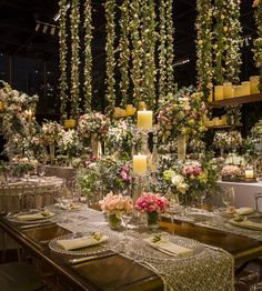 Wooden table with delicate and romantic flower arrangement and suspended swings with flowers and candles