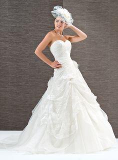 Robe de mariée romantique, habillée d'une délicate dentelle chantilly. Ses jeux de drapés offrent un ravissant décolleté cœur et soulignent la taille.  La cascade de bouillonnés de la jupe dévoile une quille de tulle.    Robe en dentelle - Laçage dos