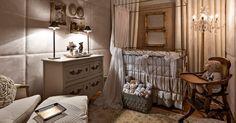 Casa Cor MG - 2013: O Quarto de Bebê, projetado pela arquiteta Flávia Zambelli Peixoto, possui paredes revestidas por tecido de toque aveludado e aparência estofada. Além do revestimento, destaque para o berço de metal com acabando dourado, equipado com dossel e cortinado de seda