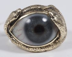 A gold ring inset with a glass eye in a gold mount surrounded by two snakes; the snakes symbolise eternity, while the eye may be a literal 'lover's-eye portrait'.  (Reeman Dansie)