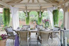 Zadaszony taras w prowansalskim stylu: wiklinowe fotele, duży drewniany stół,  brukowa kostka.