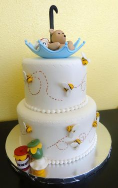 Fun little sugar paste bees and honey pots adorn this two tier fondant cake. Hand sculpted bear and umbrella are all made with edible sugar paste. Designed and crafted by Sweet Pea Cake Company in Colorado Springs.