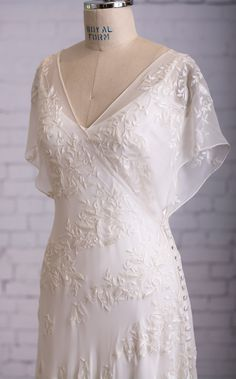 Vivian wedding dress from Martin McCrea. Front view. Flowing silk chiffon, embroidered and beaded. Asymmetrical wrap style bodice w/ kimono-style cap sleeves & side button closure. Slip dress of double silk satin. Color: Natural White