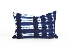 The pillow sham is made with a textile from Bamana, Mali. Traditionally men weave narrow strips of plain cotton fabric that are then pieced together into a larger rectangular cloth. Women dye the cloth in a lengthy process with natural indigo in a shibori style manner. These textiles are referred to a wrappers as they are wrapped around the body for wear. 12x18 or 14x22 Lumbar pillow. Serged / overlocked. Natural linen back panel. Invisible zipper. Synthetic Down insert. Variations in color…