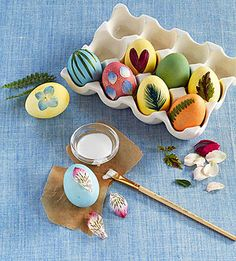 Petals, leaves, feathers, and blades of grass add to the earthy appeal of these eggs. Decorate them one at a time: paint a portion of the egg with matte Mod Podge, then place a thin natural object on the wet surface and gently smooth it in place. Apply another coat of Mod Podge on top, then let the eggs dry.