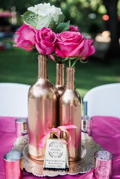 Hot pink roses and white hydrangeas. Rose Gold Wine bottle center pieces, and mercury candle holders.