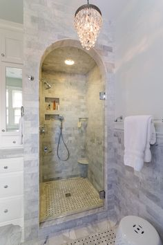 arched entry into master bath shower stall with marble subway tile