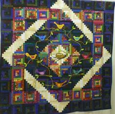 Different colorings of blocks and added applique make unique log cabin quilt. From Faith Albano