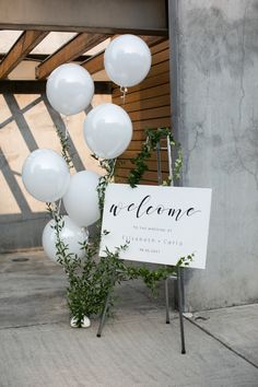 Wedding welcome sign. Simple and elegant with a touch of whimsy with the white balloons.