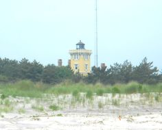 The Beautiful Hereford Inlet Lighthouse in North Wildwood in New Jersey. This photo was taken while standing on the beach and looking towards the lighthouse. All you can see is the top part with the lush greenery surrounding it.